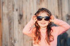 Μικρό κορίτσι που φορά υπαίθρια τα γυαλιά ηλίου Στοκ Φωτογραφίες