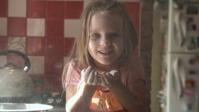 Μικρό κορίτσι που φυσά στο αλεύρι απόθεμα βίντεο