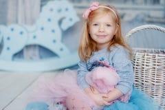 Μικρό κορίτσι που χαμογελά καθμένος στο δωμάτιό του Στοκ φωτογραφία με δικαίωμα ελεύθερης χρήσης