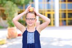 Μικρό κορίτσι που χαμογελά με τη Apple στο κεφάλι της στοκ εικόνες