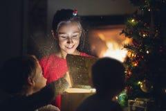 Μικρό κορίτσι που χαμογελά χαρωπά καθώς ανοίγει το χρυσό κιβώτιο δώρων στοκ φωτογραφία
