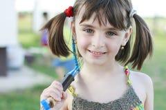 Μικρό κορίτσι που χαμογελά μετά από να παίξει την αντισφαίριση στοκ εικόνες