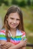 Μικρό κορίτσι που χαμογελά στο πράσινο υπόβαθρο στοκ εικόνες