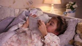 Μικρό κορίτσι που χρησιμοποιεί έναν υπολογιστή ταμπλετών φιλμ μικρού μήκους