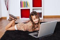 Μικρό κορίτσι που χρησιμοποιεί έναν φορητό προσωπικό υπολογιστή Στοκ εικόνα με δικαίωμα ελεύθερης χρήσης