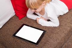 Μικρό κορίτσι που χρησιμοποιεί τη φορητή συσκευή Στοκ Εικόνες