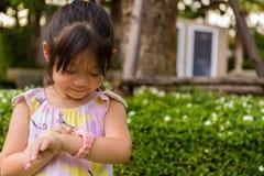 Μικρό κορίτσι που χρησιμοποιεί Smartwatch ή το έξυπνο ρολόι/νέο κορίτσι με Smartwatch ή το έξυπνο ρολόι Στοκ φωτογραφία με δικαίωμα ελεύθερης χρήσης