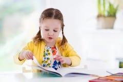 Μικρό κορίτσι που χρωματίζει και που γράφει Στοκ Φωτογραφία