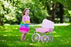 Μικρό κορίτσι που ωθεί ένα παιχνίδι stoller με την κούκλα Στοκ Φωτογραφίες
