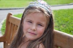 Μικρό κορίτσι, πριγκήπισσα, λυπημένη σε έναν πάγκο στο πάρκο, πορτρέτο Στοκ Φωτογραφία