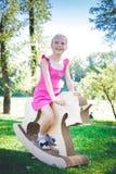 Μικρό κορίτσι σε έναν μονόκερο παιχνιδιών Χλοώδης τομέας στο πάρκο δέντρο πεδίων χαμόγελο κοριτσιών και she& x27 s ευτυχές Στοκ Φωτογραφία