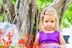 Μικρό κορίτσι σε έναν τροπικό κήπο αειθαλές μικροσκοπικό δέντρο πεύκων μπονσάι Στοκ Εικόνες