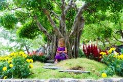 Μικρό κορίτσι σε έναν τροπικό κήπο αειθαλές μικροσκοπικό δέντρο πεύκων μπονσάι Στοκ Φωτογραφίες