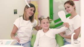 Μικρό κορίτσι σε ένα άσπρο φόρεμα και οδοντίατρος δύο που χαμογελά και που παρουσιάζει τους αντίχειρες μέχρι τη κάμερα φιλμ μικρού μήκους