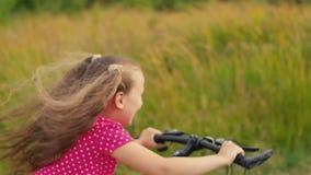 Μικρό κορίτσι σε ένα κόκκινο κοστούμι που οδηγά ένα ποδήλατο απόθεμα βίντεο