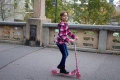 Μικρό κορίτσι σε ένα μηχανικό δίκυκλο Στοκ Φωτογραφίες