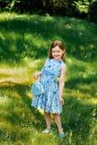 Μικρό κορίτσι σε ένα μπλε φόρεμα με μια μπλε τσάντα στο θερινό κήπο Στοκ Εικόνες