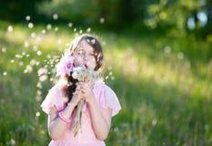 Μικρό κορίτσι σε ένα ρόδινο φόρεμα που φυσά μια ανθοδέσμη των πικραλίδων Στοκ φωτογραφία με δικαίωμα ελεύθερης χρήσης