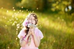 Μικρό κορίτσι σε ένα ρόδινο φόρεμα που φυσά μια ανθοδέσμη των πικραλίδων Στοκ εικόνες με δικαίωμα ελεύθερης χρήσης