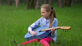 Μικρό κορίτσι σε ένα σακάκι τζιν που έχει την κιθάρα διασκέδασης και παιχνιδιού στη συνεδρίαση άνοιξης στην πράσινη χλόη ενάντια  απόθεμα βίντεο