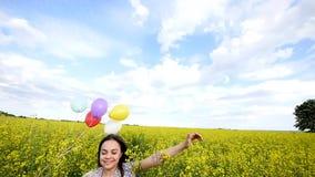 Μικρό κορίτσι σε ένα φόρεμα που τρέχει μέσω του κίτρινου τομέα σίτου με τα μπαλόνια διαθέσιμα Αργές κινήσεις φιλμ μικρού μήκους