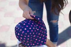 μικρό κορίτσι σε ένα όμορφο μπλε καπέλο μωρών με τις καρδιές το καλοκαίρι στοκ φωτογραφίες