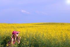 Μικρό κορίτσι σε μια κίτρινη εποχή άνοιξης λιβαδιών λουλουδιών Στοκ Φωτογραφία