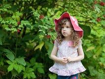 Μικρό κορίτσι σε μια κόκκινη ΚΑΠ που στέκεται στα ξύλα Στοκ Φωτογραφίες
