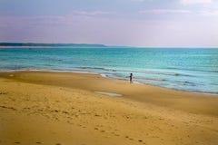 Μικρό κορίτσι σε μια παραλία κοντά στη θάλασσα στοκ εικόνες