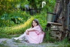 Μικρό κορίτσι σε μια ρόδινη συνεδρίαση φορεμάτων κοντά στο φρεάτιο Στοκ Εικόνες