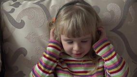 Μικρό κορίτσι στα ακουστικά που ακούει τη μουσική κίνηση Επικεφαλής κούνημα 4K υπερβολικό HD απόθεμα βίντεο
