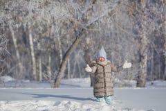 Μικρό κορίτσι στα γκρίζα παιχνίδια σακακιών με το χιόνι στο χειμερινό δάσος Στοκ Φωτογραφία