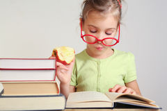 Μικρό κορίτσι στα γυαλιά που διαβάζονται το βιβλίο Στοκ φωτογραφία με δικαίωμα ελεύθερης χρήσης