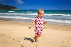 Μικρό κορίτσι στα διάστικτα τρεξίματα φορεμάτων από τη ρηχή κυματωγή κυμάτων στην παραλία Στοκ φωτογραφία με δικαίωμα ελεύθερης χρήσης