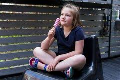 Μικρό κορίτσι στα θερινά ενδύματα που κάθεται cross-legged στην καρέκλα patio με ένα popsicle Στοκ φωτογραφία με δικαίωμα ελεύθερης χρήσης