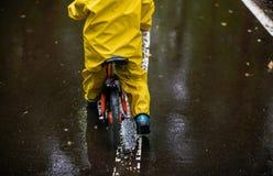 Μικρό κορίτσι στα κίτρινα αδιάβροχα ενδύματα με το ποδήλατο Στοκ Εικόνες