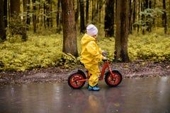 Μικρό κορίτσι στα κίτρινα αδιάβροχα ενδύματα με το ποδήλατο Στοκ Φωτογραφία