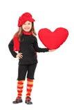 Μικρό κορίτσι στα καθιερώνοντα τη μόδα ενδύματα που κρατά μια μεγάλη κόκκινη καρδιά Στοκ Φωτογραφίες