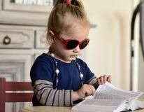 Μικρό κορίτσι στα κόκκινα γυαλιά που διαβάζει ένα βιβλίο στοκ φωτογραφία