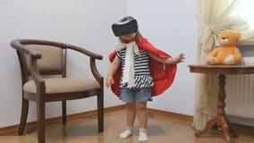 Μικρό κορίτσι στα κόκκινα παιχνίδια επενδυτών με τα γυαλιά μιας εικονικής πραγματικότητας απόθεμα βίντεο