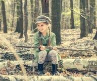 Μικρό κορίτσι στα ξύλα που κάθονται σε ένα κολόβωμα Στοκ Εικόνες