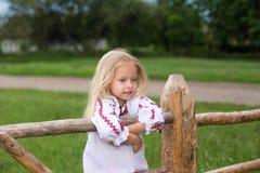 Μικρό κορίτσι στα ουκρανικά παραδοσιακά ενδύματα στο φράκτη στοκ εικόνα