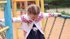 Μικρό κορίτσι στα παιχνίδια φορεμάτων στην παιδική χαρά στη θερινή ημέρα απόθεμα βίντεο