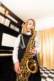 Μικρό κορίτσι στα παιχνίδια φορεμάτων στο saxophone alto Στοκ φωτογραφίες με δικαίωμα ελεύθερης χρήσης