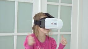 Μικρό κορίτσι στα ρόδινα παιχνίδια φορεμάτων στα εικονικά γυαλιά Clouse-επάνω απόθεμα βίντεο