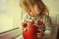 Μικρό κορίτσι στα Χριστούγεννα με την κόκκινη συνεδρίαση σφαιρών διακοσμήσεων Χριστουγέννων σε ένα παράθυρο Στοκ εικόνες με δικαίωμα ελεύθερης χρήσης
