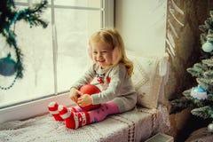 Μικρό κορίτσι στα Χριστούγεννα με την κόκκινη συνεδρίαση σφαιρών διακοσμήσεων Χριστουγέννων σε ένα παράθυρο Στοκ Φωτογραφίες