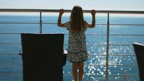 Μικρό κορίτσι στα sundress που στέκονται σε ένα ανοικτό μπαλκόνι και που εξετάζουν τη θάλασσα Στοκ φωτογραφίες με δικαίωμα ελεύθερης χρήσης