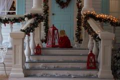 Μικρό κορίτσι στην κόκκινη συνεδρίαση φορεμάτων στη βεράντα του διακοσμημένου σπιτιού, φω'τα Χριστουγέννων, νέα παραμονή έτους `  στοκ εικόνες