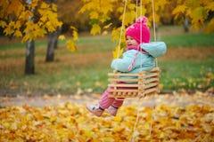Μικρό κορίτσι στην ταλάντευση στο πάρκο φθινοπώρου στοκ φωτογραφίες